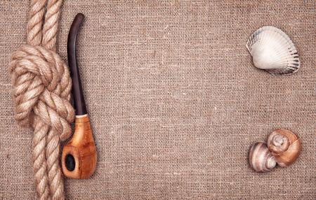 nautic: Ship rope, seashells and tobacco pipe on hessian