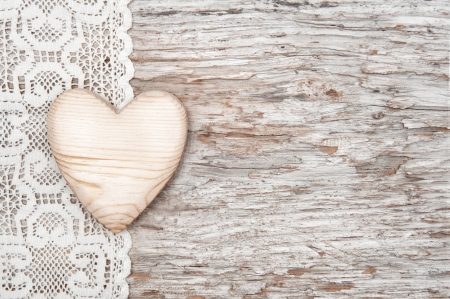 timber frame: Wooden heart on lacy cloth and old wood background Stock Photo