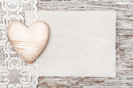 Houten hart, kanten doek en doek op oude houten achtergrond