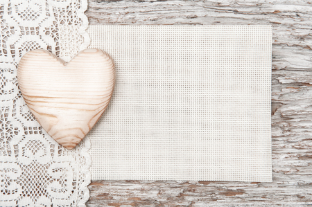 Wooden heart, lacy cloth and canvas on old wood background