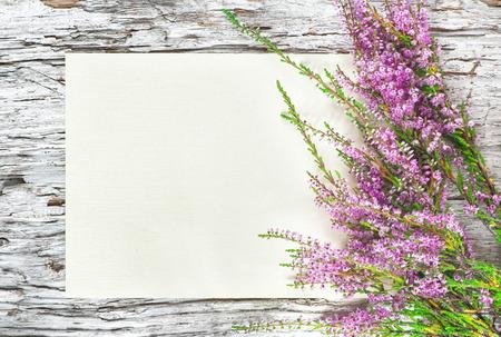 Oude ruwe houten achtergrond met papier en heide Stockfoto