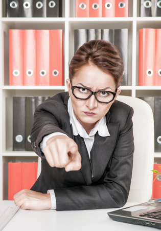 Angry woman boss pointing out at someone photo