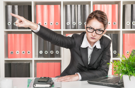 in out: Angry woman boss pointing out at someone