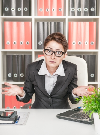 confused face: Business woman in glasses shrugs her shoulders at workplace Stock Photo