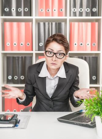 persona confundida: Mujer de negocios en vidrios se encoge de hombros en el lugar de trabajo Foto de archivo