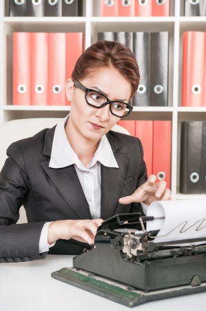 Mature business woman working with typewriter at office Stock Photo - 24681418