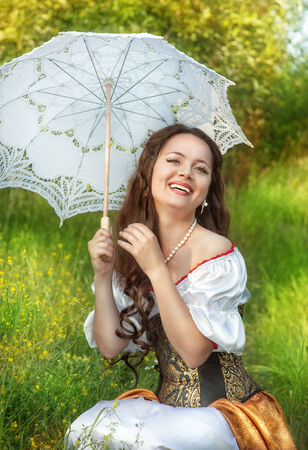 Laughing beautiful woman in vintage dress with umbrella photo