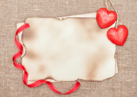 Valentine card with red wooden hearts and aged paper on burlap  photo