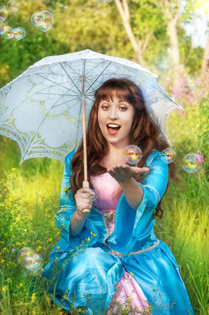 Laughing woman in medieval dress with umbrella and bubble blowers photo