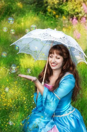 middeleeuwse jurk: Lachende vrouw in middeleeuwse kleding met paraplu en bubble blowers Stockfoto