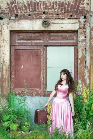 demode: Beautiful woman in the long pink vintage dress with old suitcase