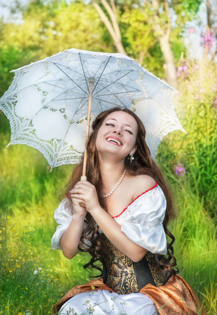 demode: Laughing beautiful woman in vintage dress with umbrella Stock Photo