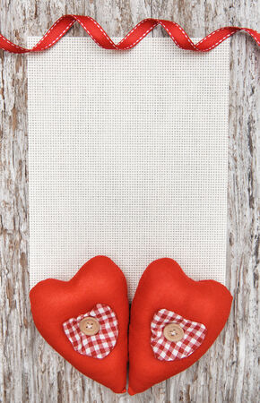 Valentine card with textile hearts on old wood background photo