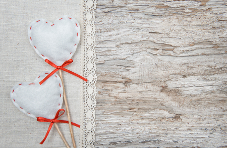 Valentine background  with textile hearts on old wood background photo