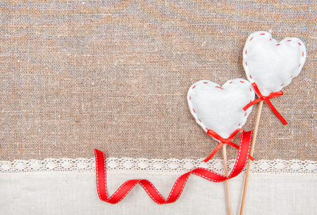 Textile hearts, ribbon and linen cloth on the burlap background photo