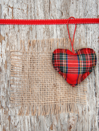 Valentine card with textile heart and sacking on old wood background photo