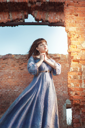 Young beautiful woman in medieval dress praying in destroyed building photo