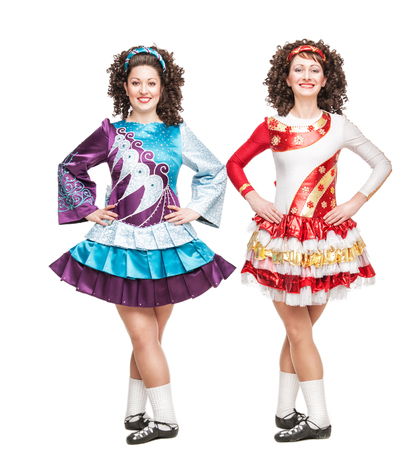 Two young women in Irish dance dresses and wigs posing isolated photo