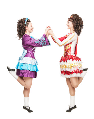 Two young women in irish dance dresses and wigs dancing isolated photo