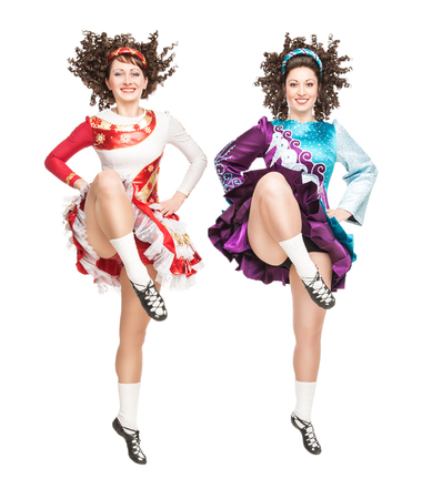 Two young women in irish dance dress and wig dancing isolated photo