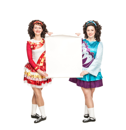 Two young women in irish dance dresses and wigs with empty paper photo