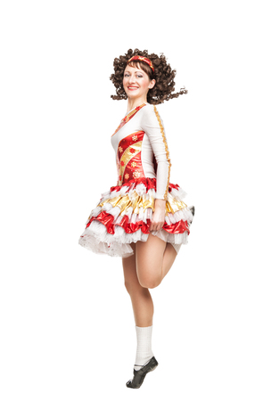 Young woman in irish dance dress and wig dancing isolated photo
