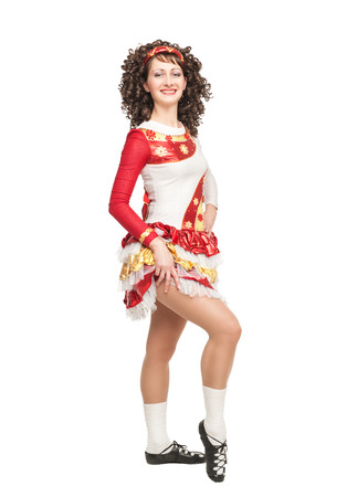 irish culture: Young woman in irish dance dress and wig posing isolated Stock Photo