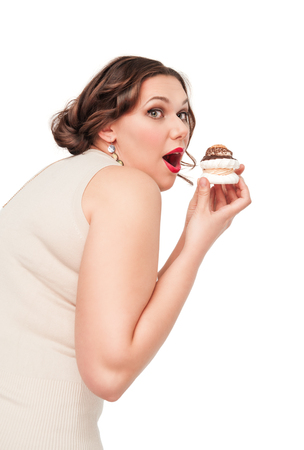 Beautiful plus size woman eating pastry isolated photo