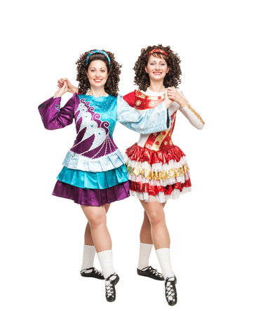 irish culture: Two young women in Irish dance dresses and wigs posing isolated Stock Photo