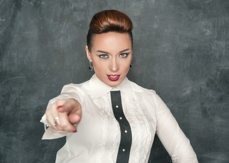 Beautiful fashion woman pointing on someone on the blackboard background