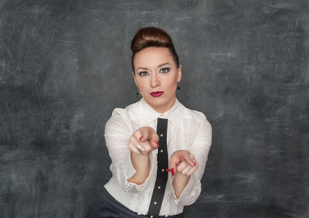 stringent: Beautiful fashion woman pointing on someone on the blackboard background