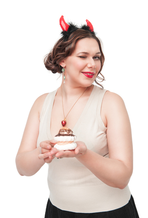Beautiful plus size woman winking and seducing with pastry isolated photo