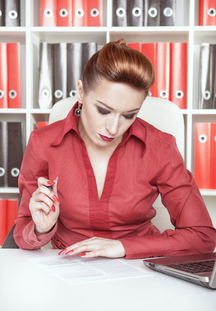 Beautiful business woman writing a report at office photo