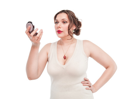 Beautiful plus size woman looking in the mirror isolated photo