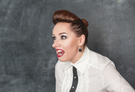 Angry screaming woman on the blackboard background Stock Photo - 25904040