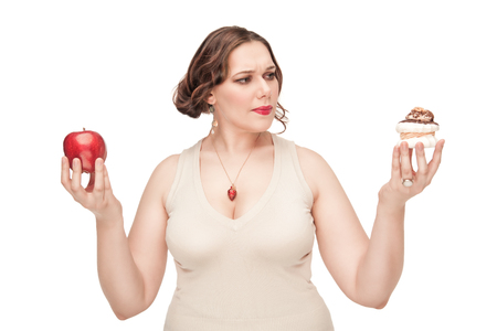Beautiful brunette plus size woman making choice between healthy and unhealthy food isolated photo