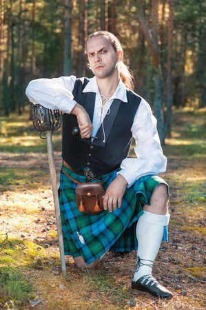 Handsome scottish man with sword and pipe outdoor