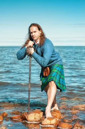 highlander: Hombre escocés hermoso con la espada en el mar