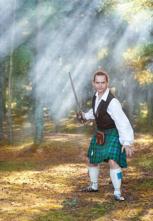 highlander: Hombre valiente escocés hermoso con la espada en el bosque con el humo