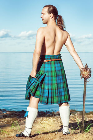 Brave man with sword in scottish costume near the sea photo