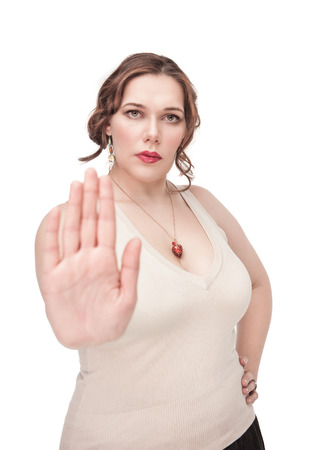 disinclination: Beautiful plus size woman making stop gesture isolated