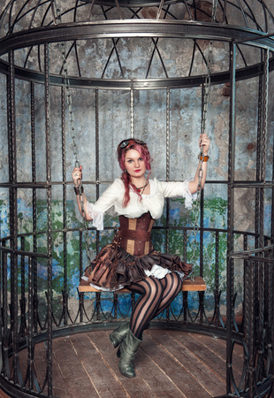 Beautiful steampunk woman with pink hair sitting in the metal cage photo