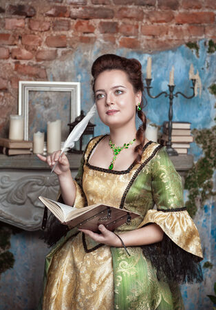 Beautiful young  woman in long medieval dress writing in diary near fireplace photo