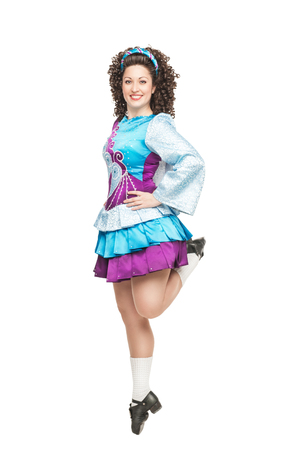 Young woman in irish dance dress, hard shoes and wig dancing isolated photo