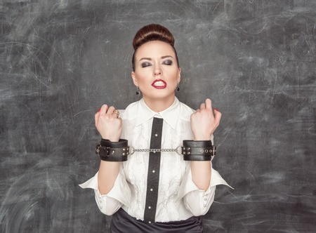 Business woman with handcuffs on the blackboard background photo