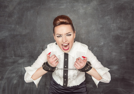 Screaming business woman with handcuffs on the blackboard background photo