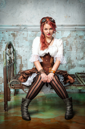 steampunk goggles: Beautiful steampunk woman with pink hair sitting on the metal bed