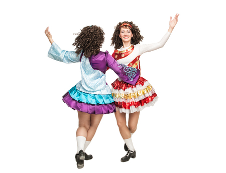 Two irish dancers in hard shoes and wig dancing isolated photo