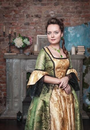 middeleeuwse jurk: Mooie jonge vrouw in lange middeleeuwse kleding dichtbij open haard
