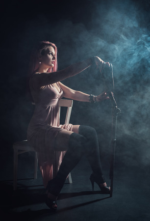 Beautiful young woman with rifle sitting on the chair in the smoke photo